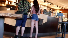 One side of couple waiting for their coffee inside Starbucks store Stock Footage