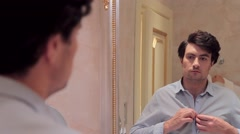 Man dressing up and looking himself in mirror Stock Footage