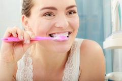 Woman brushing cleaning teeth. Oral hygiene. Stock Photos