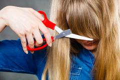 Woman cutting her fringe. Stock Photos