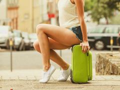 Part body of female tourist with suitcase. Stock Photos