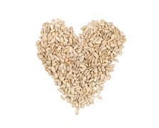 Shelled sunflower seeds heart shaped heap on white Stock Photos