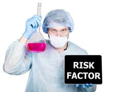 Doctor in surgical uniform, holding flask and digital tablet pc with risk factor Stock Photos