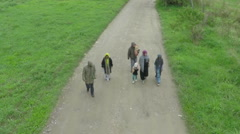 Migrant family, parents and children passing on dirty road, drone shot by Sheyno Stock Footage