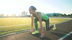 Slow motion. Young beautiful woman getting ready to run at the stadium Stock Footage