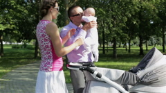 Young parents taking their baby from the pram Stock Footage