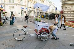 Girl sets the counter with a refrigerator, attached to the bike Stock Photos