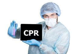 Doctor in surgical uniform, holding test tube and digital tablet pc with cpr Stock Photos