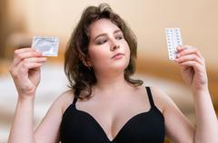 Young sexy woman holds condom and contraceptive hormonal pills in hands and s Stock Photos