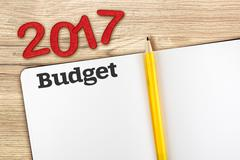 Top view of 2017 new year red number with budget open notebook and yellow pen Stock Photos