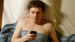 Caucasian young man types by mobile phone in a bed Stock Footage
