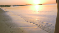 Legs girls go on the beach at sunset. HD Stock Footage