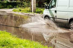 Commercial vehicle riding on big puddle on the road Stock Photos