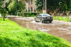 Car riding on big puddle on the road Stock Photos