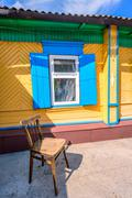 Simple wooden stool next to an old wooden yellow and blue painted house Stock Photos