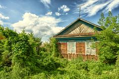 Overgrown abandoned wooden cottage in dense thick lush green undergrowth Stock Photos