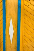 Hand painted wood with ornate details in blue, yellow and white traditional s Stock Photos
