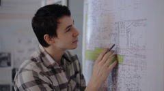 Smart man is carefully analyzing layout which is hung on wall in office Stock Footage