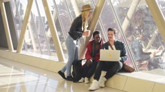 3 young adults entrepreneurs or students group mixed race around laptop havin Stock Footage