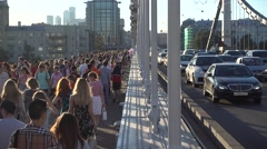 Crowd of people and cars move along the bridge Stock Footage