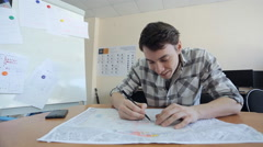Young man sits at wooden table and creates blueprint Stock Footage