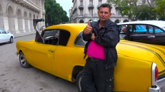 A man takes pride in his old classic car on the streets of Havana, Cuba. Stock Footage