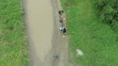 Beautiful drone shot, people migrants passing on muddy road with puddle. Sheyno. Stock Footage
