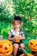 Halloween. Child dressed in black drinking pumpkin cocktail, trick or treat.  Stock Photos
