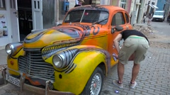 A man spray paints his classic old car on the streets of Havana, Cuba. Stock Footage