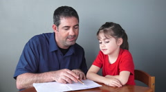 Father helping his daughter with her school project Stock Footage