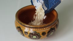 Pouring oat flakes into a bowl Stock Footage