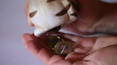 Man pulls coins from piggy bank. Open the cap and pours them into the palm. Stock Footage