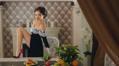 Woman in evening dress puts his foot on the table and posing Stock Footage