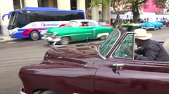 Classic old cars are driven through the colorful streets of Havana, Cuba. Stock Footage