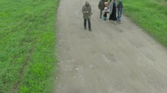 Exhausted family, migrants passing on dirt road, drone shot, slow motion, Sheyno Stock Footage