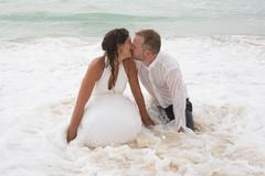 Romantic newly-married couple.Young groom kissing his bride in sea Stock Photos
