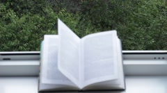 Book in front of a window in a wind Stock Footage