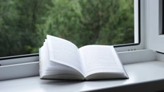 Book in front of a window in a garden Stock Footage