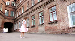 Girl in pink dress swirls in the yard Stock Footage
