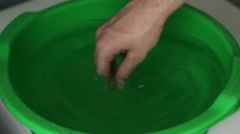 Touching water in a green basin Stock Footage