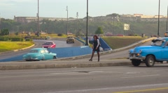 A woman walks along a highway in Cuba. Stock Footage