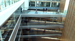 Time lapse of business people walking along different floors of large Stock Footage