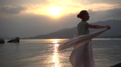 Young woman wears a white stole on the beach background at sunset. Slow motion Stock Footage