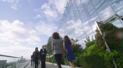 Businesswoman walking outdoors on London office terrace with city views Stock Footage