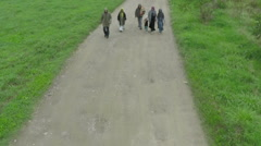 Immigrants, young family walks on muddy road, drone shot, slow motion by Sheyno. Stock Footage