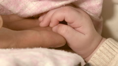Mother and newborn daughter in maternity home. Hand in hand Stock Footage