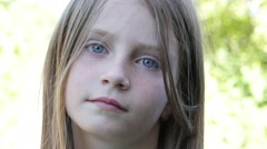 Beautiful blonde young girl in nature, portrait close up Stock Footage