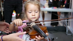 Child little girl try play violin - music instrument educative demonstration  Stock Footage