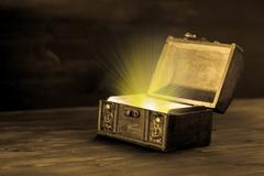 Beautiful fairytale concept of retro chest with light miracle on wooden plank Stock Photos