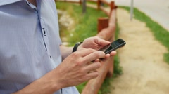 Man using mobile smart phone in park, iphon style Stock Footage